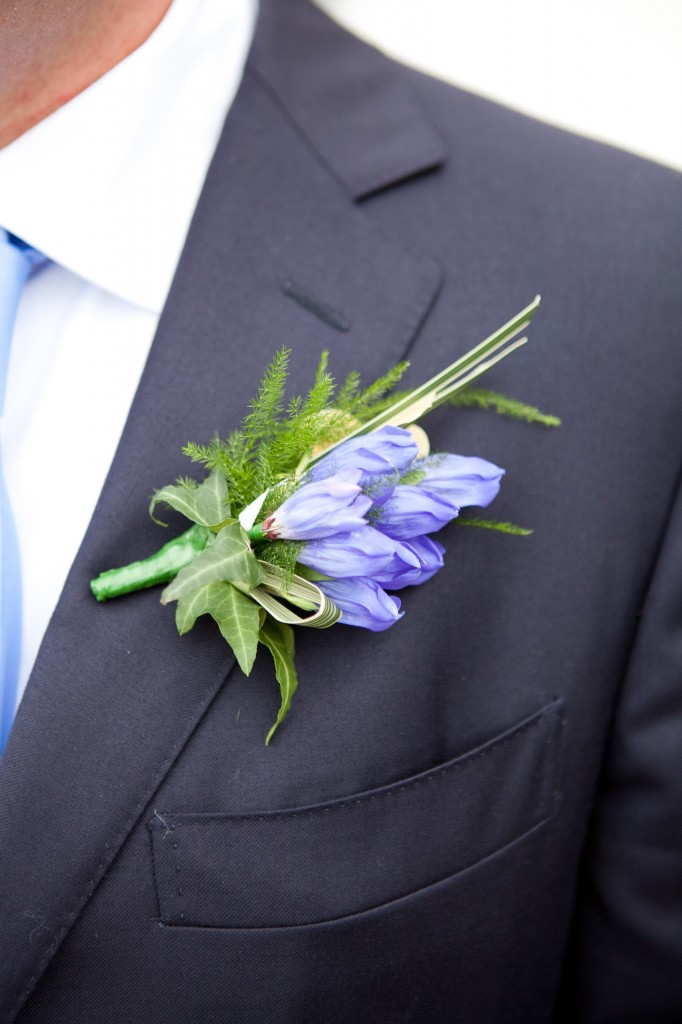 A groom wears a gentian buttonhole at a wedding in Cornwall.