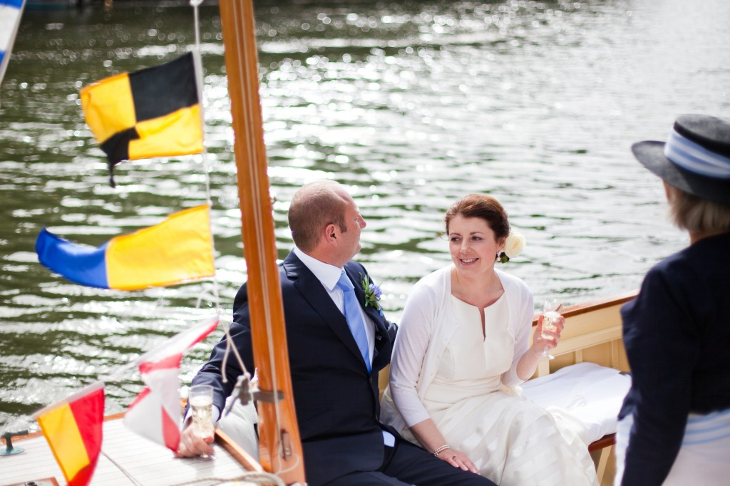 Bride on a boat wearing a cardigan over her wedding dress